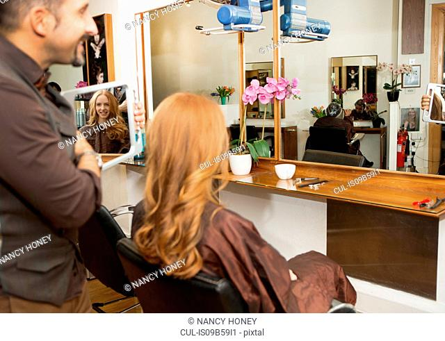 Hairdresser showing customer styled long red hair in salon