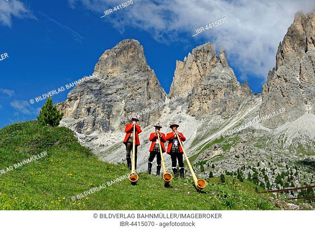 Alphorn players in front of mountains Langkofel and Plattkofel, local costume group, Fest zur ladinischen Einheit 1946, Sella, Dolomites, South Tyrol, Italy