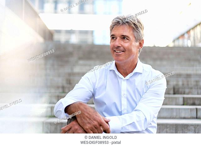 Portrait of confident mature businessman sitting on stairs