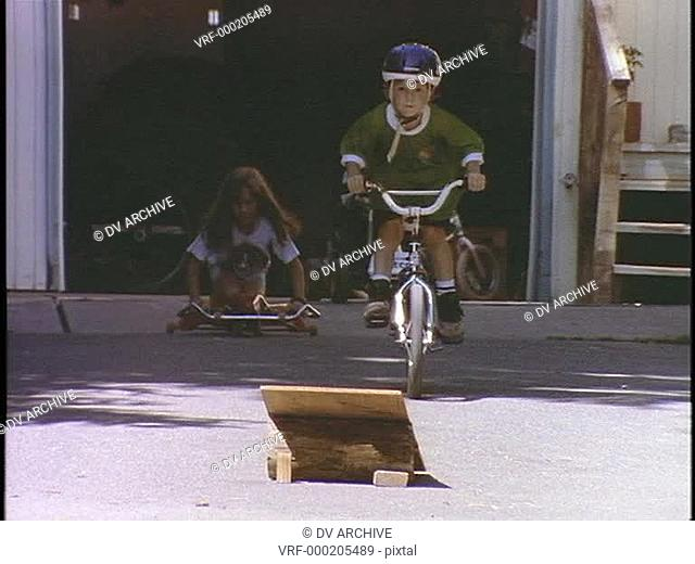 Children ride and jump ramps on bicycles and toy vehicles