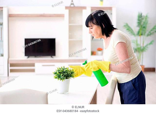 Old mature woman tired after house chores