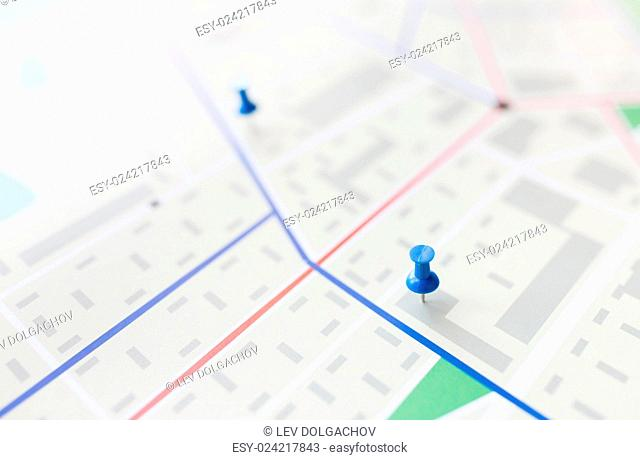 cartography, location and navigation concept - close up of map or city plan with pin