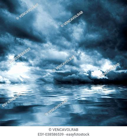 Dark storm clouds before rain above the water level. Natural background