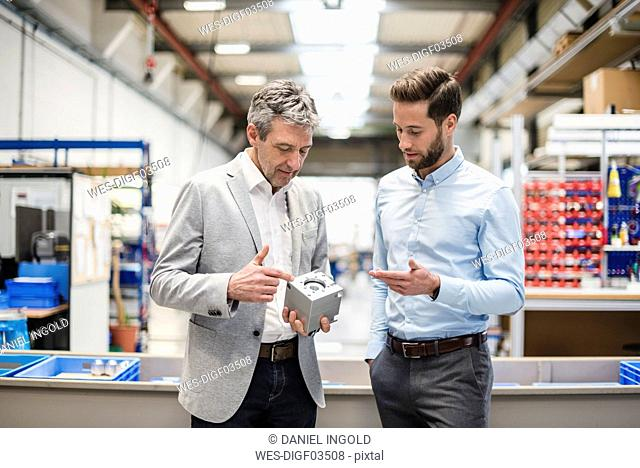Businessmen during meeting with a product in production hall