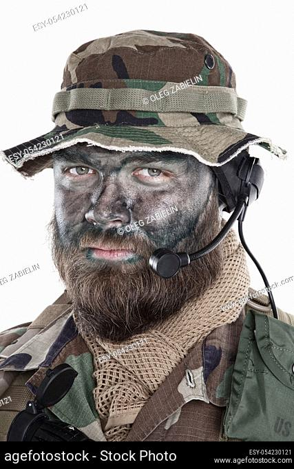 Shoulder studio portrait of commando soldier, modern mercenary, professional soldier with black camouflage paint on bearded face