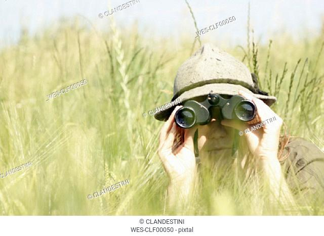 Young woman using binoculars in wheat field