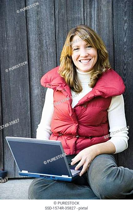 Happy woman working on a laptop and smiling