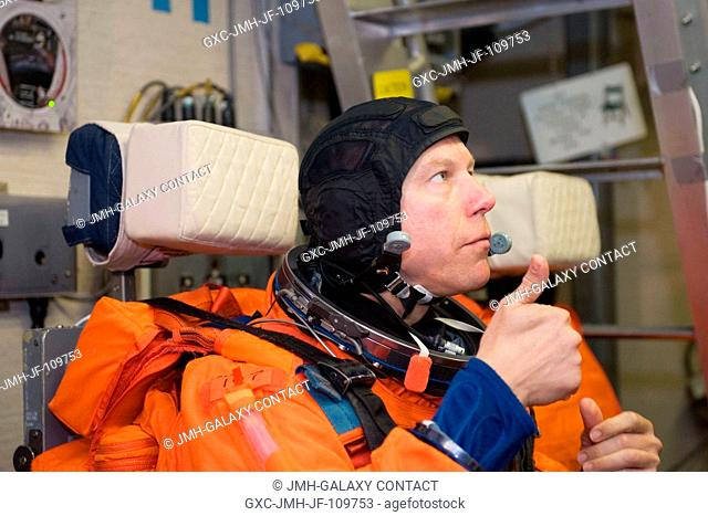 Astronaut Tim Kopra, STS-127 mission specialist, attired in a training version of his shuttle launch and entry suit, gives a thumbs-up signal during a training...