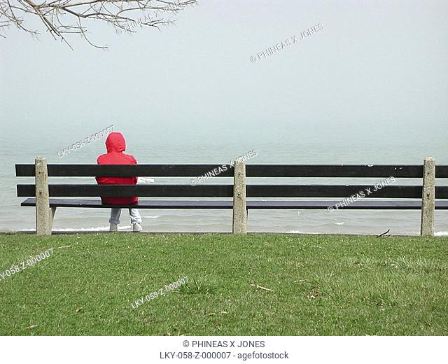Person in red hooded coat sits on park bench near water's edge