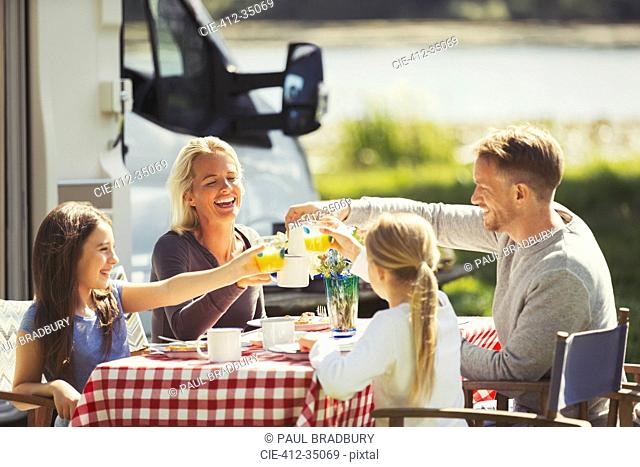 Family toasting coffee and orange juice glasses at table outside sunny motor home