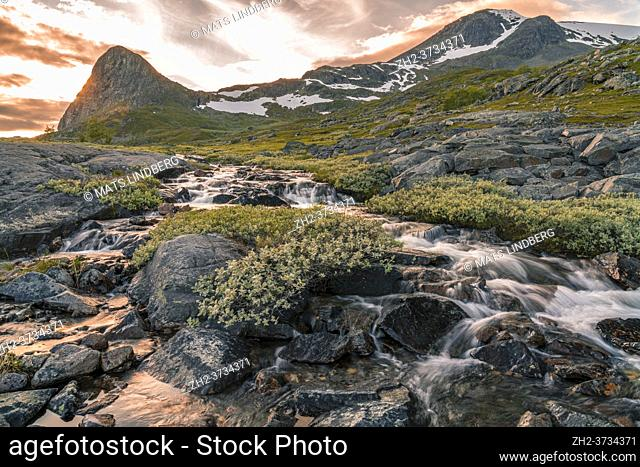 Waterfall with mountains in background with snow on them, evening light with nice colored sky, Gällivare county, Stora sjöfallet nationalpark, Swedish Lapland