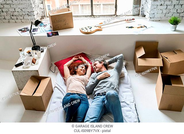 Couple moving into industrial style apartment, lying on mattress