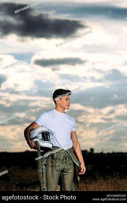 Man posing dressed as an astronaut on a meadow with dramatic clouds in the background