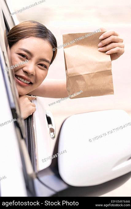 Asian Young adult in car holding disposable bag for take out food from drive thru service restaurant. Drive thru is new normal and popular service after...
