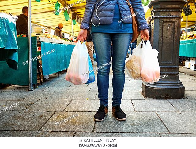 Young woman at market, holding bags of shopping, low section