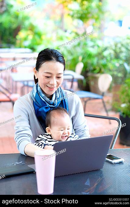 Woman working with laptop with holding baby