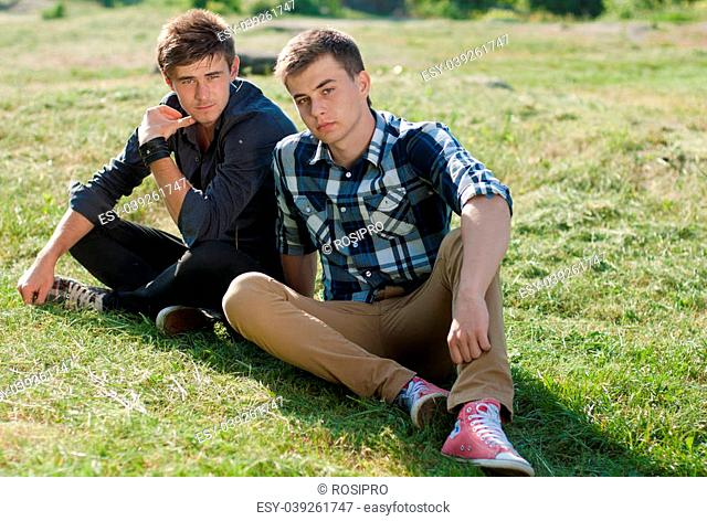 Two young handsome man sitting back to back outdoors