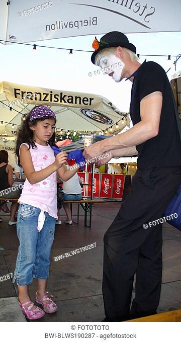 street performer enchanting little girl