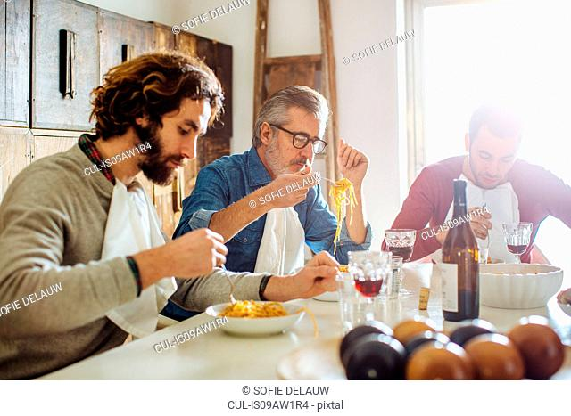 Mature man and adult sons eating spaghetti lunch at dining table