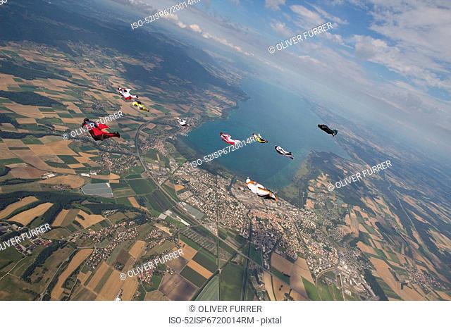 People skydiving over rural landscape