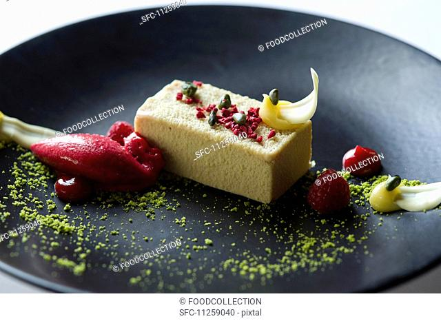 A slice of pistachio cake with raspberry sorbet
