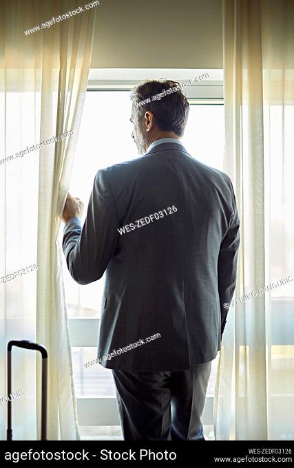Businessman in hotel room looking out of window