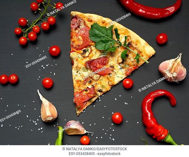 triangular piece of baked pizza with mushrooms, smoked sausages, tomatoes and cheese, black background, flat lay