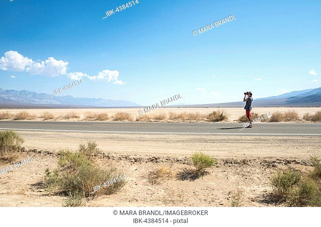 Young man standing on road, photographing, Highway 190, Death Valley National Park, California, USA