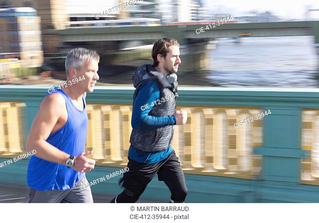 Male runners running on sunny urban bridge