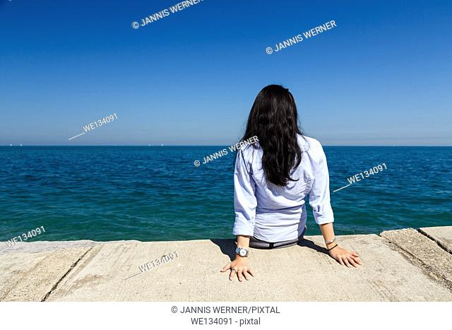 Young Asian woman sits at Lake Michigan in the Hyde Park area of Chicago, IL, USA on a sunny day