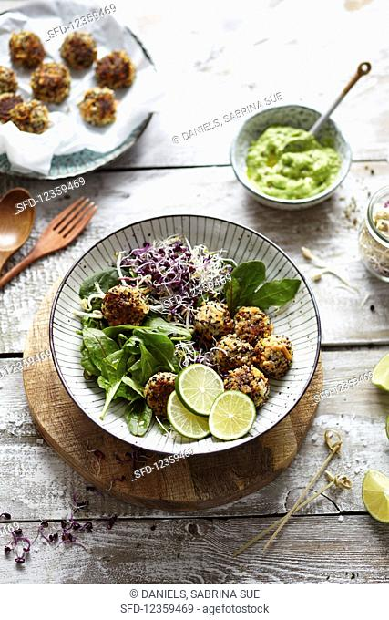 Quinoa and carrot balls with a lime and avocado dip and sprout salad
