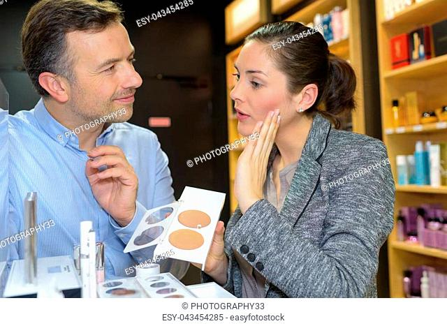 saleswoman and man shopping for girlfriend
