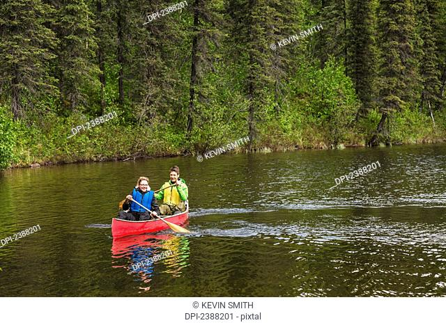 Couple in red canoe on Byers Lake with green tree covered shoreline in the background, Denali State Park; Alaska, Alaska, United States of America
