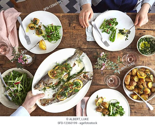 Stuffed baked trout with herbs and lemon, roasted baby potatoes, salsa verde and green salad
