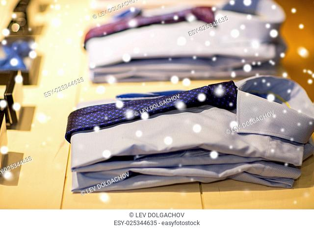 sale, shopping, male fashion, style and wear concept - close up of shirts with ties at clothing store over snow