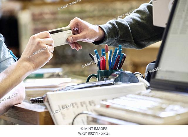 Closeup of hands exchanging a credit card during a retail sale next to a computer at the front desk of a retail shop