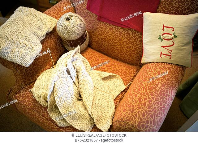 Knitting handmade with a ball of wool on a chair with a small cushion hand embroidered with the word LOVE