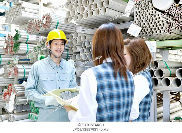 Warehouse Worker Talking to Two Female Colleagues