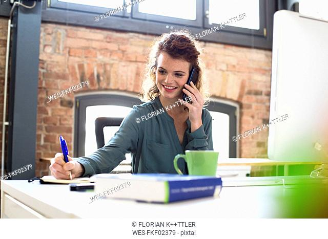 Young woman on the phone at desk in office