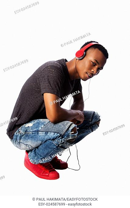 Handsome African teenager listening to music wearing red headphones while squatting, on white