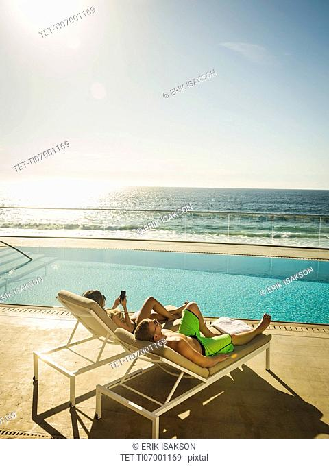 Couple relaxing by swimming pool by ocean