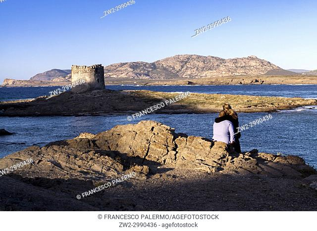 Rear view of a couple on rocks looking across sea at derelict lighthouse at dusk. La Pelosa, Sardinia. Italy