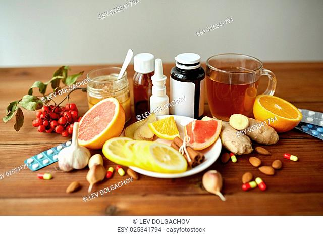 healthcare, traditional medicine, flu and ethnoscience concept - drugs on wooden table