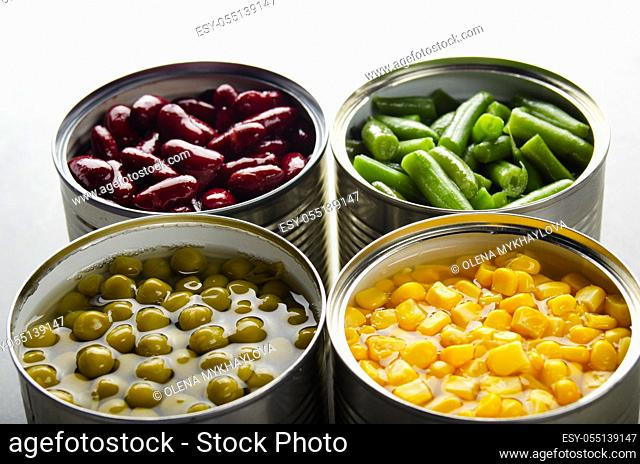 Canned kidney beans, green beans, peas and corn in opened tin cans on kitchen table. Non-perishable foods background
