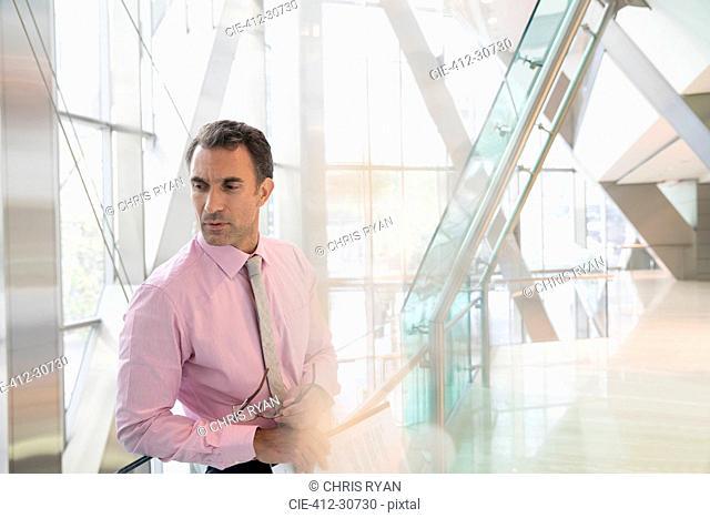 Pensive corporate businessman looking down in modern office lobby