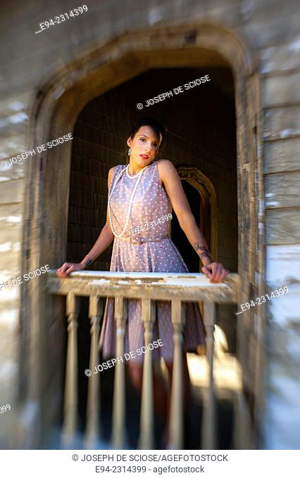 Portrait of a 30 year old brunette wearing a dress and a pearl necklace looking at the camera leaning over a porch railing of an old house