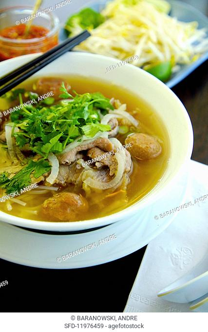 Pho Dac Biet (noodle soup, Vietnam) with beef, rice noodles, bean sprouts, limes and basil