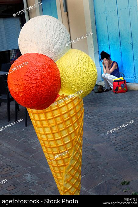 A woman talks on her phone behind a huge advertising ice cream cones sculpture