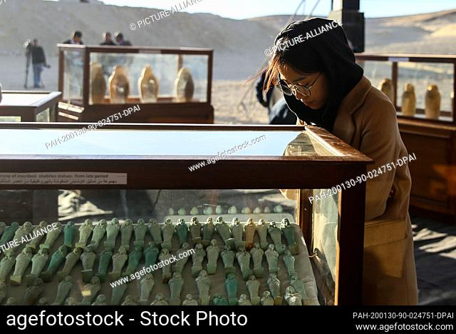 30 January 2020, Egypt, Minya: A woman looks at artifacts found in newly discovered three communal tombs of the high priests of ancient Egyptian deity Djehuty...