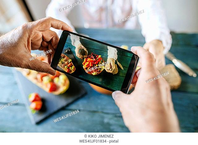 Close-up of man's hands taking a picture with mobile phone eating salad of tomato, pomegranate, papaya and olives, with papaya with fruits on the side and with...
